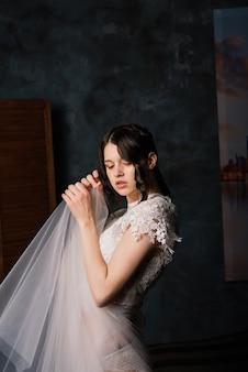 Mooie bruid in witte lingerie zit in haar slaapkamer