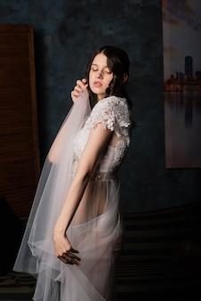 Mooie bruid in witte lingerie zitten in haar slaapkamer en studio. ochtend van het huwelijksconcept