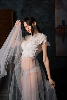 Mooie bruid in witte lingerie zitten in haar slaapkamer