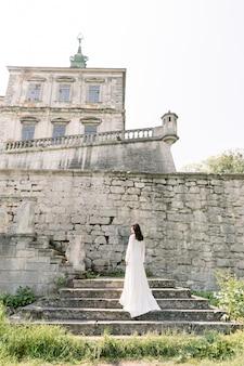 Mooie bruid in witte trouwjurk staat op de stenen trap