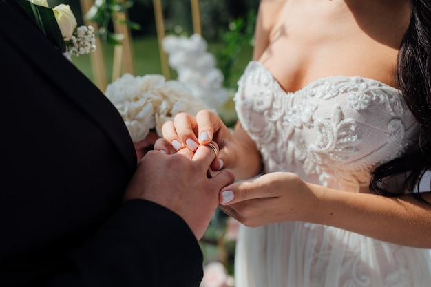 Mooie bruid in witte trouwjurk zet op de vinger van de bruidegom de trouwring