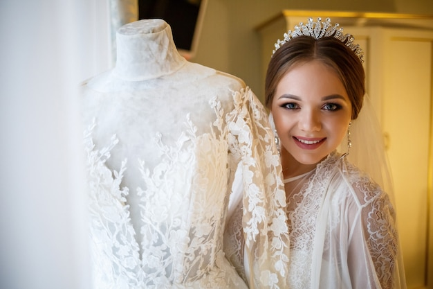 Mooie bruid kleedt haar witte trouwjurk aan