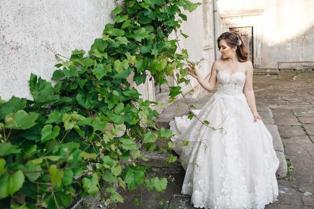 Mooie bruid loopt rond het oude gebouw