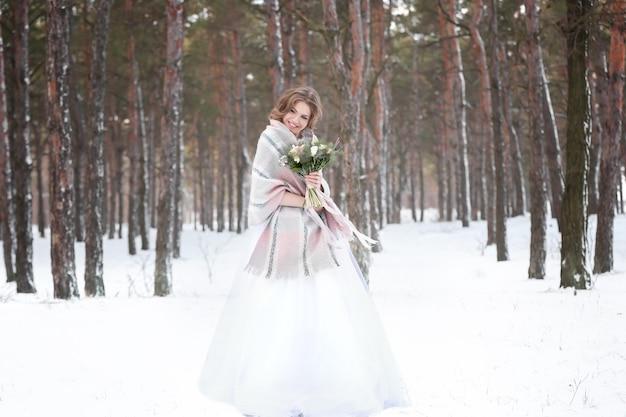 Mooie bruid met boeket buiten op winterdag