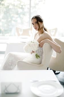 Mooie bruid met een boeket in de hand zit in de huwelijksdag van een restaurant