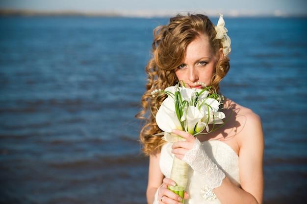 Mooie bruid met een boeket van calla lelies aan de kust van de rivier in de zomer professionele make-up en kapsel
