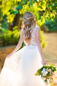 Mooie bruid met een bruidskapsel en een bruidsboeket in de rug in een groene tuin