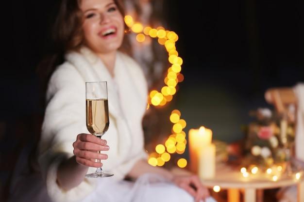Mooie bruid met glas champagne buiten op winteravond