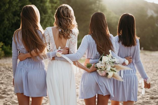 Mooie bruid met haar bruidsmeisje op de bruiloft op het strand