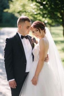 Mooie bruid met haar knappe bruidegom die buiten op theri huwelijksdag loopt. gelukkig jonggehuwden