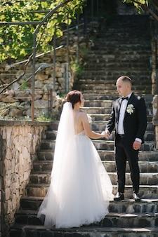 Mooie bruid met haar knappe bruidegom die buiten op theri huwelijksdag loopt.
