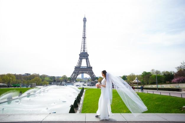 Mooie bruid met huwelijksboeket van lavendel het stellen op de aard.