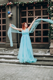 Mooie bruid met rood haar in een blauwe lange jurk op de achtergrond van de stad