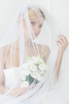 Mooie bruid met sluier en boeket