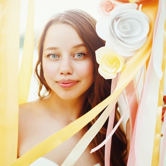 Mooie bruid onder papieren bloemendecoratie