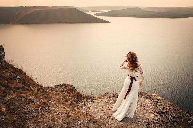 Mooie bruid op een achtergrond van bergen en rivier