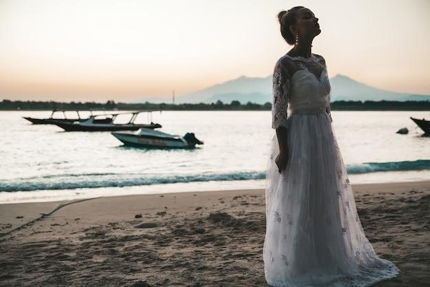 Mooie bruid op het strand achter zee bij zonsondergang