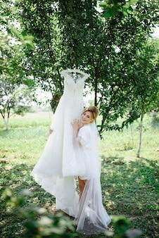 Mooie bruid peignoir poseren in de buurt van haar trouwjurk. de jurk hangt aan een boom in de tuin