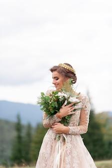 Mooie bruid poseren in haar trouwjurk op een achtergrond van bergen. in haar handen houdt ze een boeket wilde bloemen.