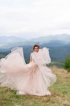 Mooie bruid poseren in haar trouwjurk op een achtergrond van bergen.