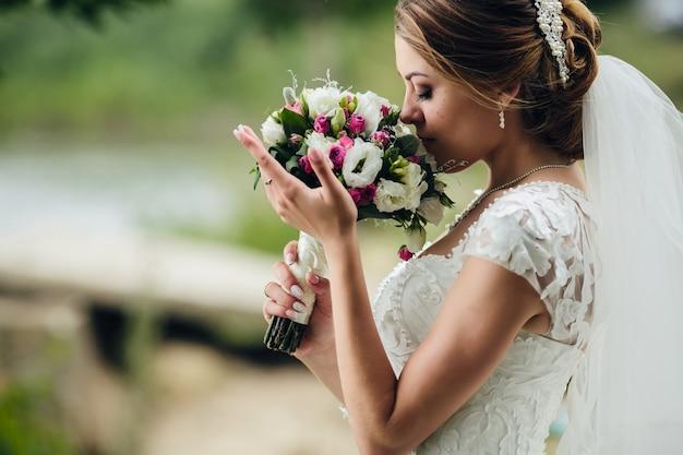 Mooie bruid ruikende bos