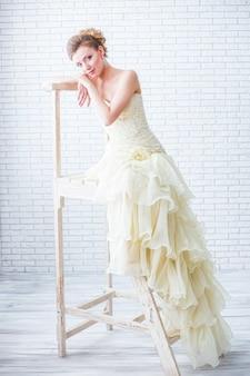 Mooie bruid staat bij het raam uperevshis op de ladder.