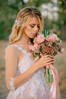 Mooie bruid staat met een boeket in handen op een natuur-achtergrond