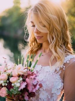Mooie bruid staat met een boeket in handen op een natuur