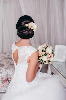 Mooie bruid terug met elegante bruiloft kapsel, jurk en bloemen
