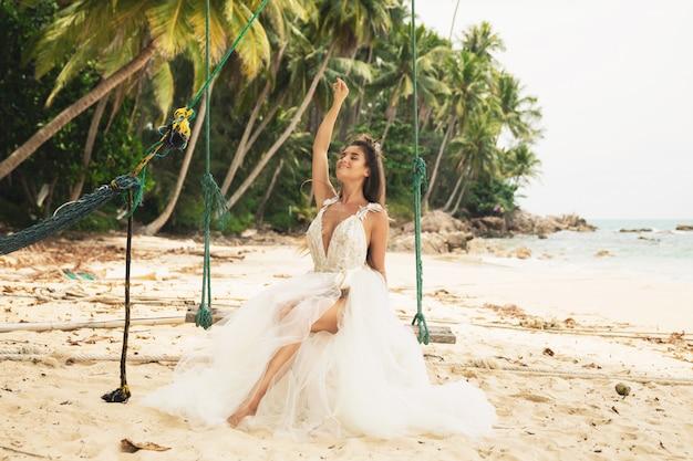 Mooie bruid trouwjurk dragen op het tropische strand