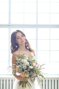 Mooie bruid vrouw in elegante trouwjurk met boeket bloemen