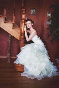 Mooie bruid zittend op houten trappen