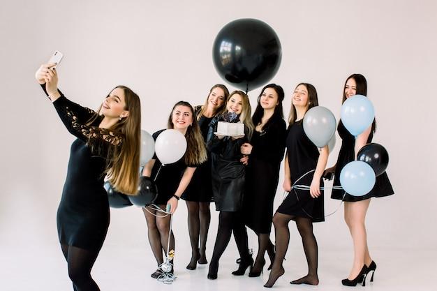 Mooie bruidsmeisjes in zwarte jurken met aantrekkelijke aanstaande bruid die selfie op smartphone maakt, geniet van een verjaardagsfeestje met cake en luchtballonnen, plezier maakt, lacht en lacht. partij concept