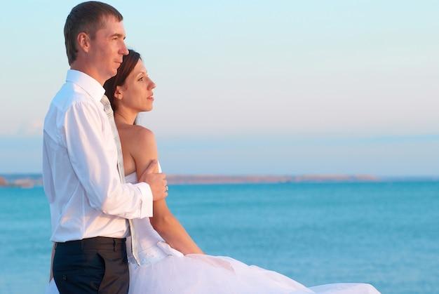 Mooie bruidspaar-bruid en bruidegom knuffelen op het strand. pas getrouwd