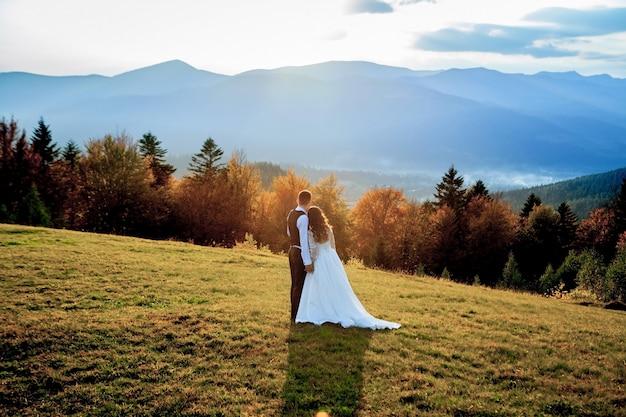 Mooie bruidspaar, bruid en bruidegom, verliefd op bergen. de bruidegom in een mooi pak en de bruid in een witte luxe jurk. bruidspaar loopt