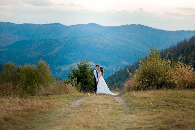 Mooie bruidspaar, bruid en bruidegom, verliefd op de bergen. de bruidegom in een mooi pak en de bruid in een witte luxe jurk. bruidspaar loopt