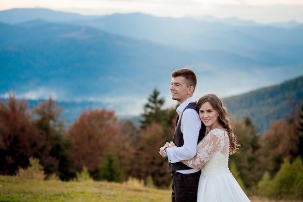 Mooie bruidspaar, bruid en bruidegom, verliefd op de muur van bergen. de bruidegom in een mooi pak en de bruid in een witte luxe jurk. bruidspaar loopt