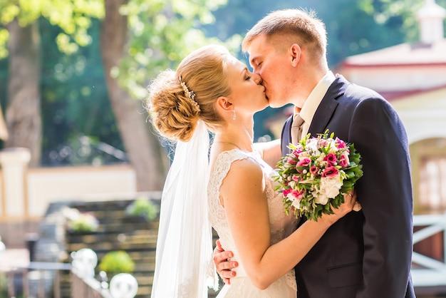 Mooie bruidspaar buitenshuis. ze kussen en omhelzen elkaar