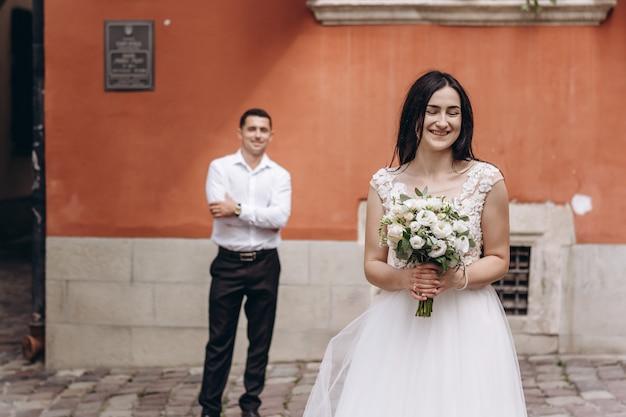 Mooie bruidspaar in de buurt van de oranje oude stenen muren.