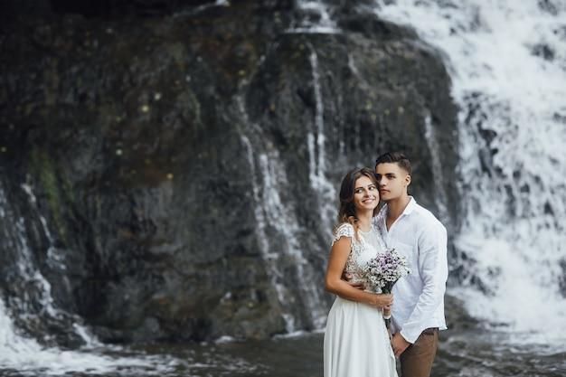 Mooie bruidspaar in de buurt van prachtige waterval