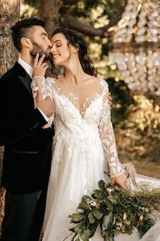 Mooie bruidspaar jonggehuwden knuffelen op de achtergrond van het bos.