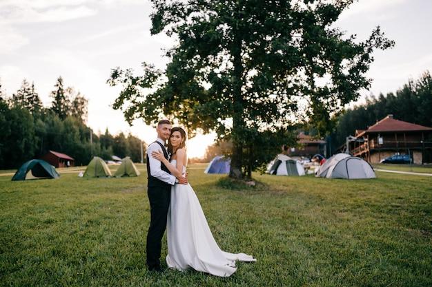 Mooie bruidspaar knuffelen buiten bij zonsondergang.