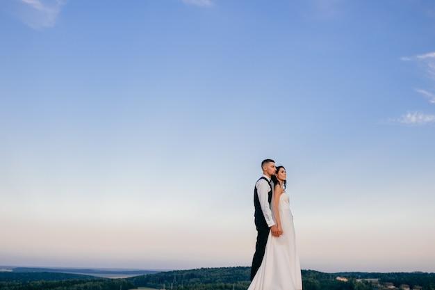 Mooie bruidspaar knuffelen buiten.