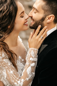 Mooie bruidspaar lachen en kussen op de achtergrond van stenen.