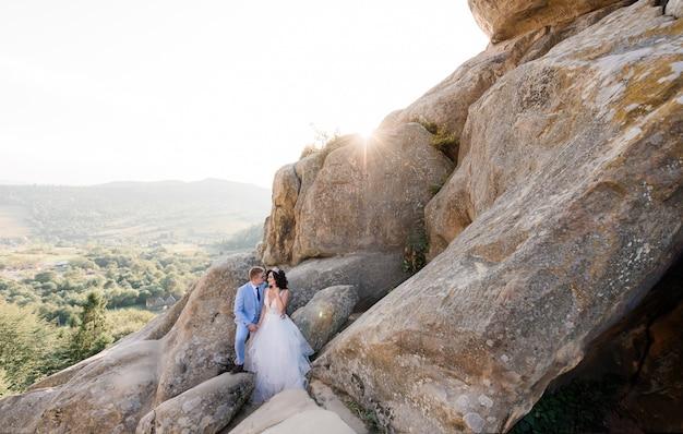 Mooie bruidspaar op de zonnige dag staat op de enorme rotsen met een schilderachtig uitzicht op een bos
