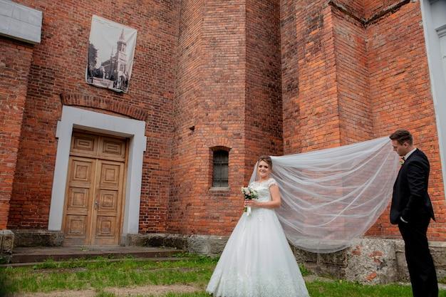 Mooie bruidspaar poseren in de buurt van de muur