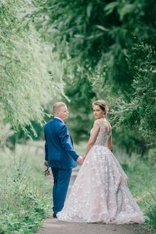 Mooie bruidspaar poseren in de natuur.