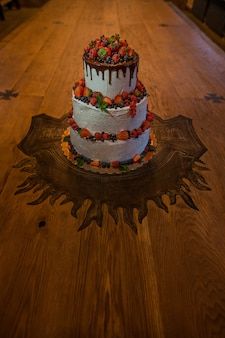 Mooie bruidstaart bedekt met witte glazuur, donkere chocolade en