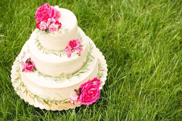 Mooie bruidstaart met bloemen, buitenshuis. drie niveaus