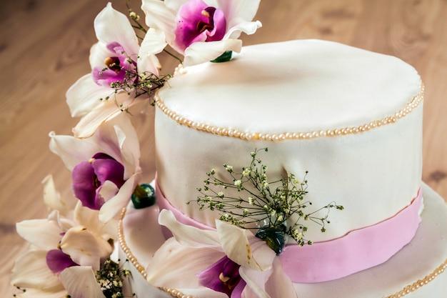 Mooie bruidstaart met bloemen, close-up van cake met blurr